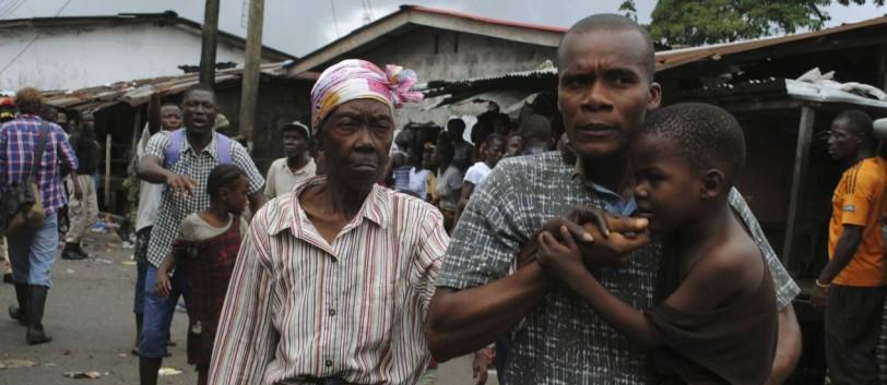 Residentes de área isolada em Monróvia, na Libéria, tentam fugir durante protestos reprimidos por forças policiais - STRINGER / REUTERS