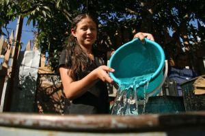 Menina enche um recipiente com água em Honduras. / BANCO MUNDIAL