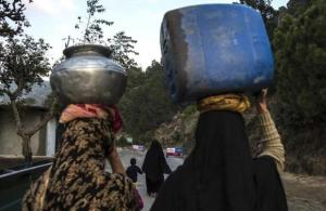 Women carry water as they walk on Margalla Hills in Islamabad