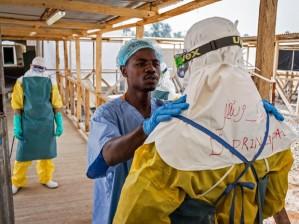 Imagem de 2 de março mostra funcionário preparando colega com roupa de proteção contra o ebola em clínica de Makeni, em Serra Leoa (Foto: Michael Duff/Associated Press)