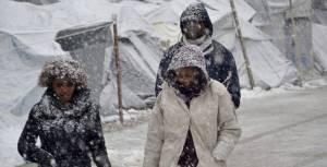 Varios refugiados caminan bajo la nieve en el campamento de refugiados de Moria, en Lesbos, la pasada semana. STRATIS BALASKAS EFE